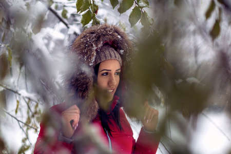 Winter snowy  tree forest .Young smiling girl enjoying the snowy mountains at  holiday.