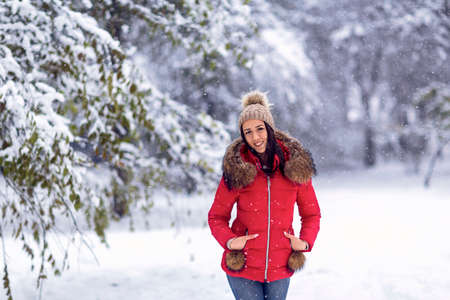 Beautiful smiling  woman standing among snowy trees in winter forest and enjoying snow. Standard-Bild