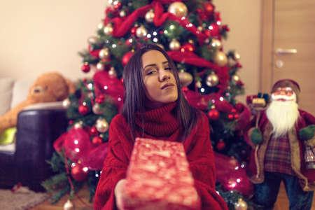 Christmas  gift for you. Woman holding Christmas gift box and smiling