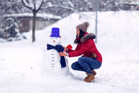 Happy woman playing with a snowman on winter day.Wintertime. Happy holiday. Standard-Bild