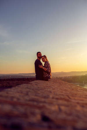Smiling loving couple watching the sunset