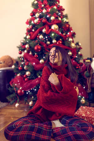 Happy young woman and Christmas gifts on floor at home.Christmas holiday Standard-Bild