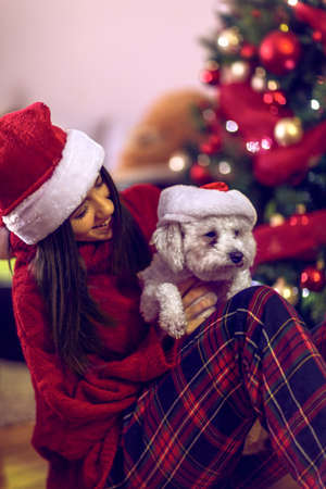 smiling young girl in santa hats embracing cute puppy.Cute dog for Christmas gift.