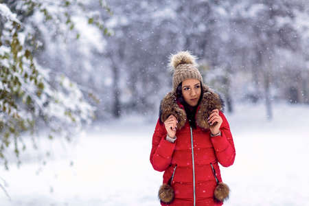 young woman enjoying in the snow.Happy girl standing outdoors in snow during winter. Standard-Bild