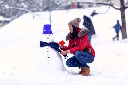 Happy woman playing with a snowman on winter day. Standard-Bild