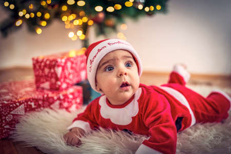 lovely baby boy in santa claus costume in Christmas room on Christmas day.