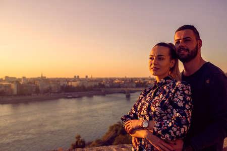 happy couple enjoying together on romantic sunset.