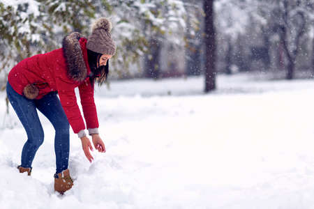 Girl playing with snow. Beautiful young woman in winter. Wintertime. Happy woman holds snowball in hands.