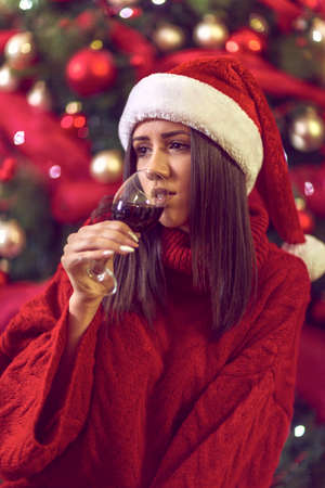 holidays, winter and people concept - young smiling woman in Santa hat by Christmas tree at home. Standard-Bild