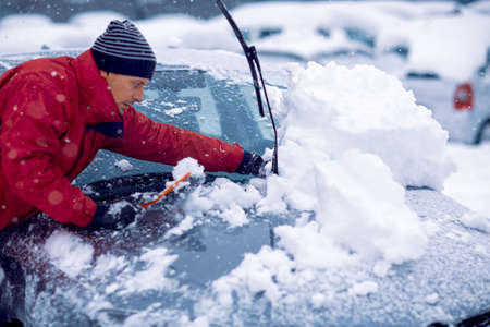 Winter problems of car drivers.man brushing the snow off his car on a cold winter day Standard-Bild