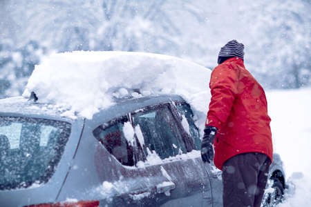 Car stuck in snow. man brushing the snow off his car on a cold winter day