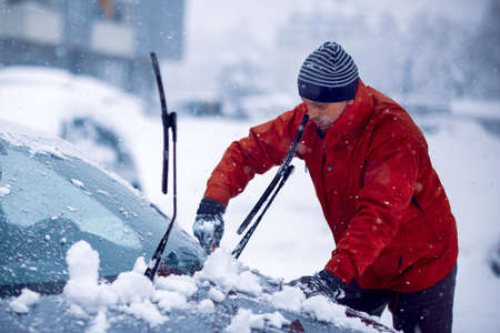 Frozen car covered snow at winter day.cleaning car windshield of snow winter.Man clears snow from icy windshield of car.