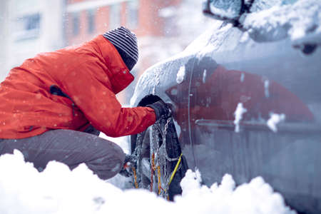Snow chains on the wheels of car.Man preparing car for travelling at winter snowy day. Standard-Bild
