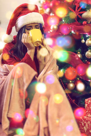 Smiling woman sitting by the christmas tree and drinking hot tea Standard-Bild