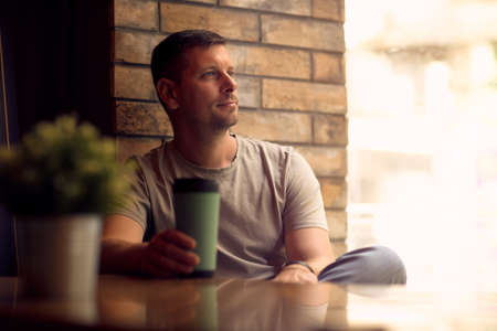 Smiling man drinking coffee in a coffee shop and looking through a window