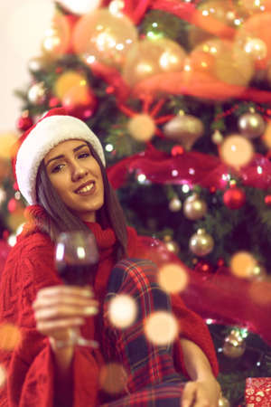 Woman toasting with red wine.holidays, winter and people concept - young smiling woman in Santa hat by Christmas tree at home.