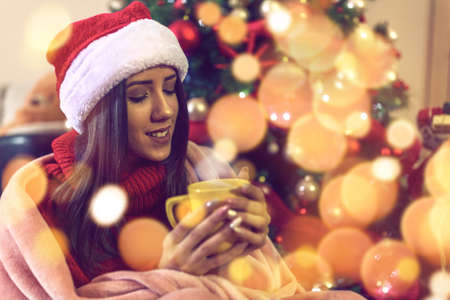 young woman in Santa hat drinking tea or coffee over christmas tree background at home