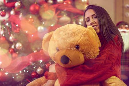 young beautiful woman with Christmas gift.Happy Girl hugs teddy bear present