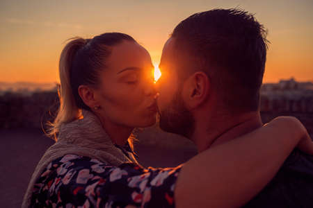 Young man and woman in love kissing at evening  in sunset