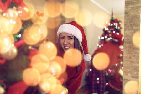 Smiling Girl and decorating beautiful christmas tree Standard-Bild