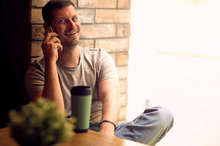 Smiling Young Man using smartphone in cafe.Man  relaxing in  cafe .Freelancer. Standard-Bild