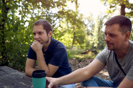 Young Men sitting in the park and enjoying peaceful sunny day Standard-Bild