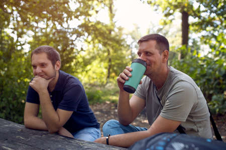 Young Men sitting in the park and enjoying peaceful sunny day and  drink coffee