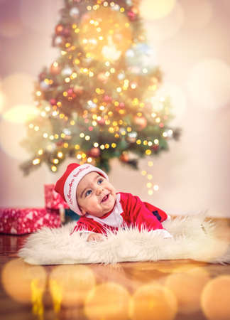 Cute smiling baby boy in Christmas costume and gift box on floor at home Standard-Bild