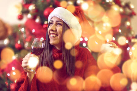 young smiling woman in Santa hat by Christmas tree at home toasting with red wine.