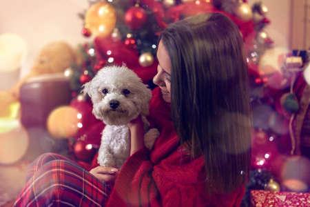 smiling young woman embracing cute dog at Christmas holiday