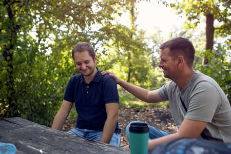 Smiling Men enjoying peaceful sunny day in nature