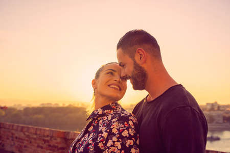 cheerful young couple kissing outdoor at the sunset