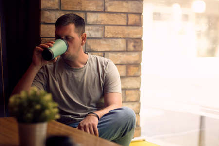 young man in restaurant.Man drinking coffee in cafe