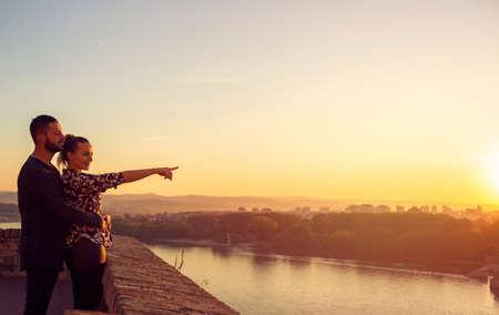 Smiling loving man and woman watching the sunset Standard-Bild