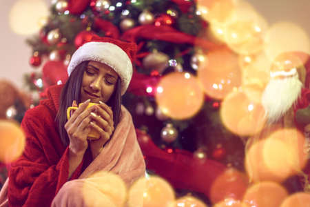Smiling girl sitting by the christmas tree and drinking hot tea