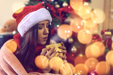 young girl in Santa hat drinking tea or coffee over christmas tree background at home