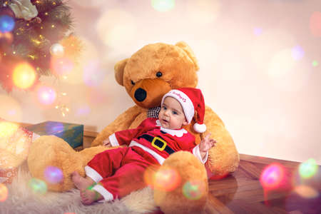 Little baby boy in Christmas Santa's costume with teddy bear  on Christmas day.Happy baby boy wearing santa clothes.