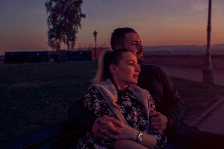 Smiling young man and woman hugging at evening the sunset Standard-Bild