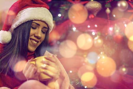Smiling girl in Santa hat drinking tea  over christmas tree background at home Standard-Bild