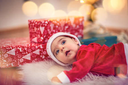 Cute smiling baby in Santa hat on floor at home. Christmas celebration