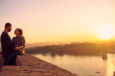 Smiling young  man and woman spend time together at sunset Standard-Bild