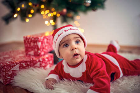 Cute smiling baby in Christmas costume and gift box on floor at home
