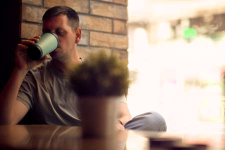 Young man in cafe.Man  relaxing in  cafe.Man drinking coffee in cafe Standard-Bild