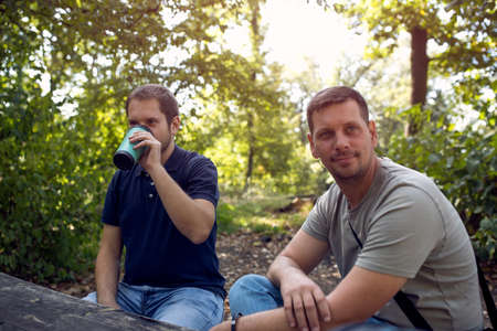 Smiling Men enjoying peaceful sunny day in nature and  drink coffee