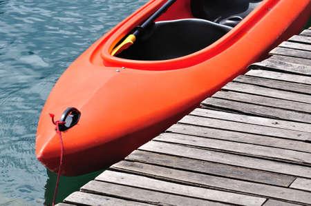 Orange kayak floating on lake beside wooden dock