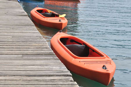 Two orange kayak beside wooden dock photo