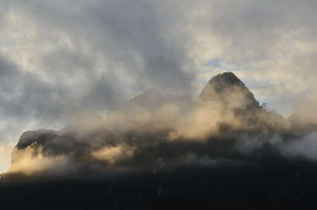 Silhouette of limestone mountain cover with mist in morning