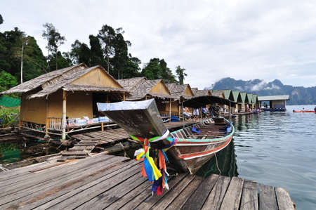 Long tailed boat floating on lake with bamboo hut Stock Photo