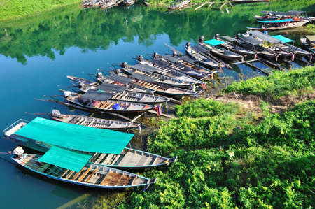 Group of long tailed boats floating on green emerald lake