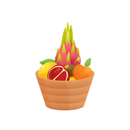 Juicy colorful fruit in wooden bowl isolated over white background. Package with pitahaya, cut pomegranate, apricot, lemon, kiwi. Autumn harvest or diet, healthy food concept